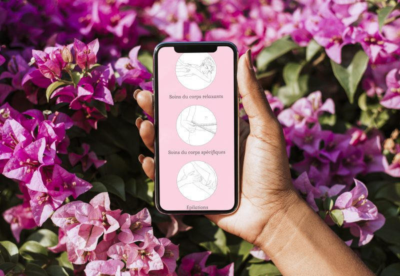 Woman holding a mockup phone over a pink bougainvillea